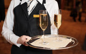 Female waiter with champagne flutes — Stock Photo