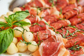 Tapas with cured ham, basil and melon balls — Stock Photo