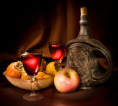 Wine with original clay bottle, persimmon an apple — Stock Photo