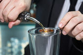 Bartender pouring alcohol in measuring spoon — Stock Photo
