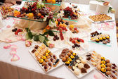 Banquet table full of sweets, fruits and berries — Stock Photo