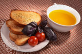 Toasts, olive oil, basil grass and tomatos — Stock Photo