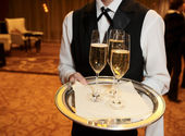 Male waiter with champagne flutes — Stock Photo