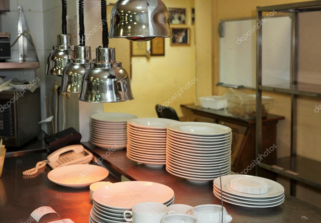 Output zone of a commercial kitchen with infrared lamps to keep plates warm — Stock Photo #12473338