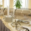 Table with dishware and shiny marmites — Stock Photo #12813264