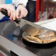 Chef frying seabass fillet — Stock Photo