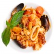 Pasta with tomato sauce and seafood in plate — Stock Photo #12815136