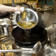 Chef is pouring cooking oil in wok — Stock Photo