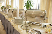 Table with dishware and shiny marmites — Stok fotoğraf
