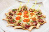 Canapes with ham and salmon caviar tartlets — Stock Photo