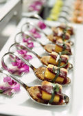 Canapes with cured ham on banquet table — Stock Photo