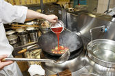 Chef is pouring sour sauce in wok — Stock Photo