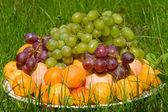 Hög med färsk frukt i gräs — Stockfoto