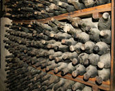 Cellar full of dirty wine bottles — Stock Photo