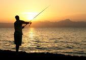 Man fishing in last rays of sunlight — Stock Photo