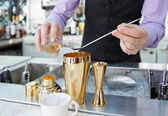 Bartender is adding ingredient in shaker — Stock Photo