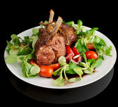 Rare fried rack of lamb isolated on black — Stock Photo