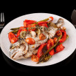 Roasted gilt-head bream with vegetables on plate, isolated on bl — Stock Photo