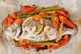 Dorade with vegetables roasted in culinary paper — Stock Photo