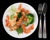Grilled salmon steaks in plate, isolated on black baclground — Stock Photo