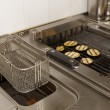 Stock Photo: Deep fryer and grill on commercial kitchen