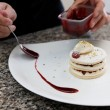 Pastry chef is decorating the dessert with berry sauce — Stock Photo