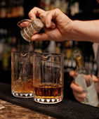 Bartender is pouring whisky in glass — Stock Photo