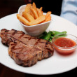 Stock Photo: Waiter offering T-bone steak with french fries
