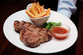 Waiter offering T-bone steak with french fries — Stock Photo