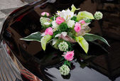 Wedding boquet on expensive car cowl — Stock Photo