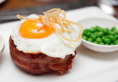 Tenderloin steak with fried egg and green pies, british dish — Stock Photo