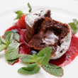 Stock Photo: Chocolate fondant with berry sauce cut in halves