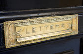 Brass letterbox slot in old door — Stock Photo