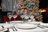 Place setting with Christmas tree in background — Stock Photo