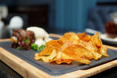 Potato chips and meat on table — Stock Photo