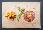 Beef tartare with french fries and avocado — Stock Photo