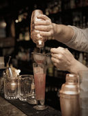 Bartender is straining cocktail — Stock Photo