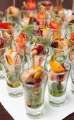 Various snacks in shot glasses — Photo