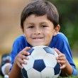 Young hispanic boy lying down with soccer ball — ストック写真