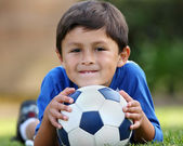 Young hispanic boy lying down with soccer ball — Stock Photo