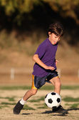 Boy playing soccer in late afternoon light — Stock Photo
