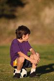 Rapaz sentado na bola de futebol — Foto Stock