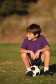 Boy sitting on soccer ball — Stock Photo