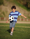 Latino boy playing with soccer ball — Stock Photo