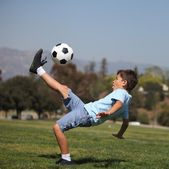 Boy kicking fußball — Stockfoto