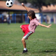 Stock Photo: Boy playing soccer or football in the park