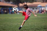Boy playing soccer in the park — Stok fotoğraf