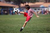 Chłopiec grać w piłkę nożną w parku — Zdjęcie stockowe