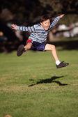 Garoto feliz pulando no parque — Foto Stock