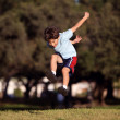 Stock Photo: Happy young boy jumping and playing in park